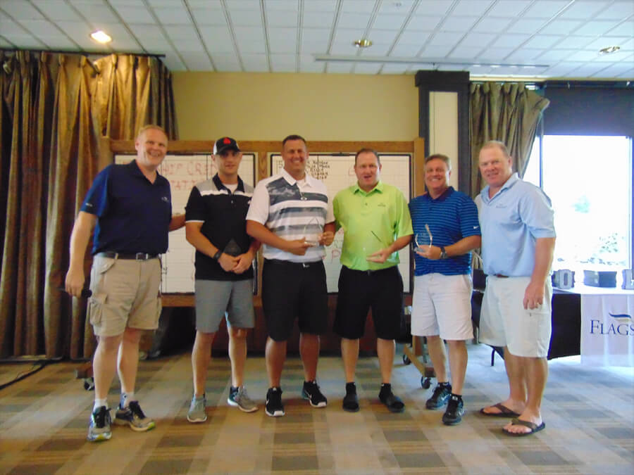 six golfers pose in the clubhouse with trophies