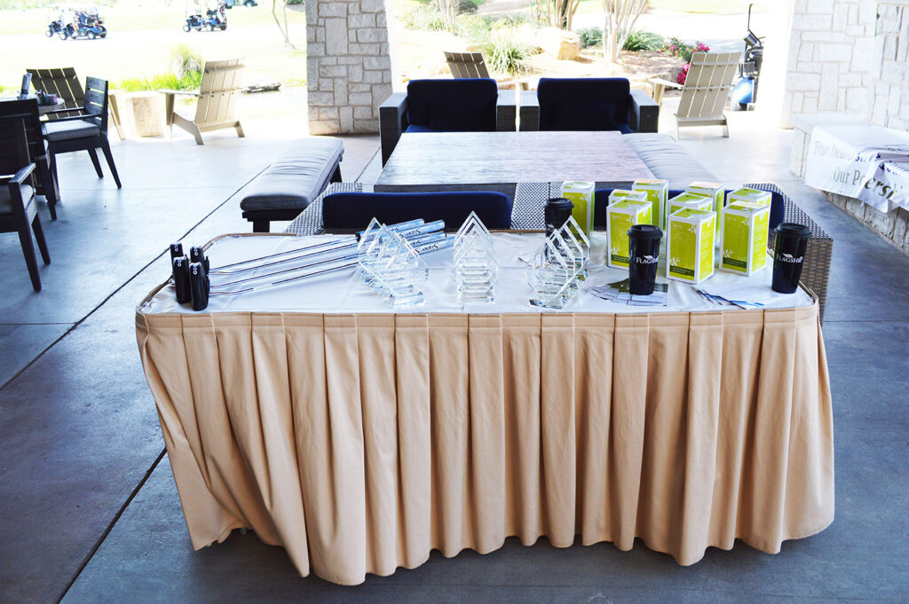 a table covered with golf clubs, Flagship cups and trophies