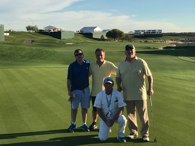 four golfers pose on the green