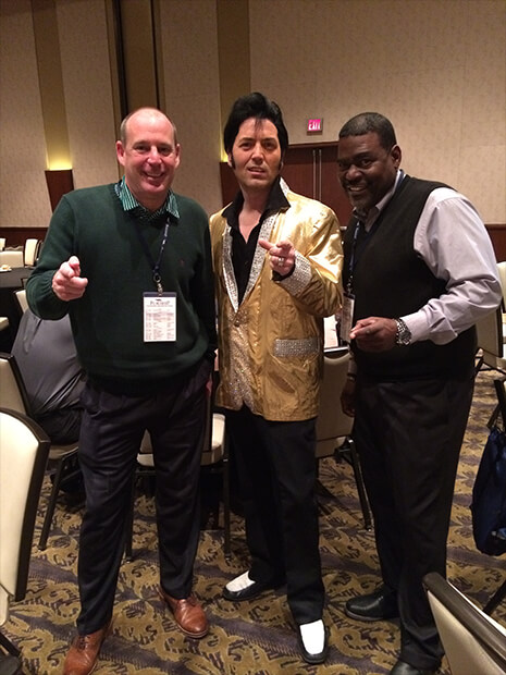 two attendees pose with an Elvis impersonator