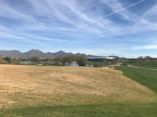 a view of the golf course with mountains in the background