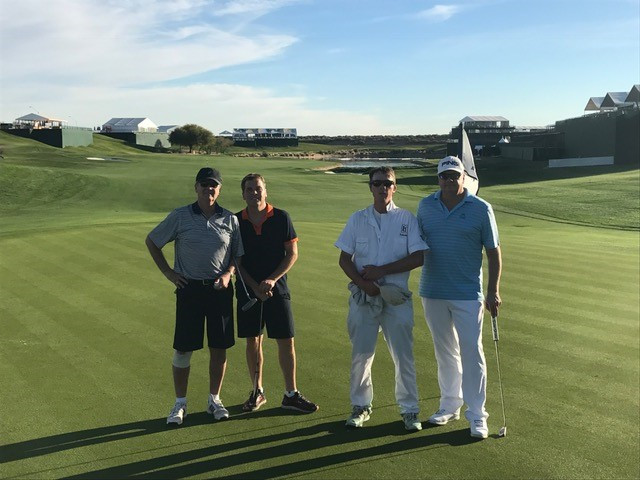 four golfers take a different pose on the green