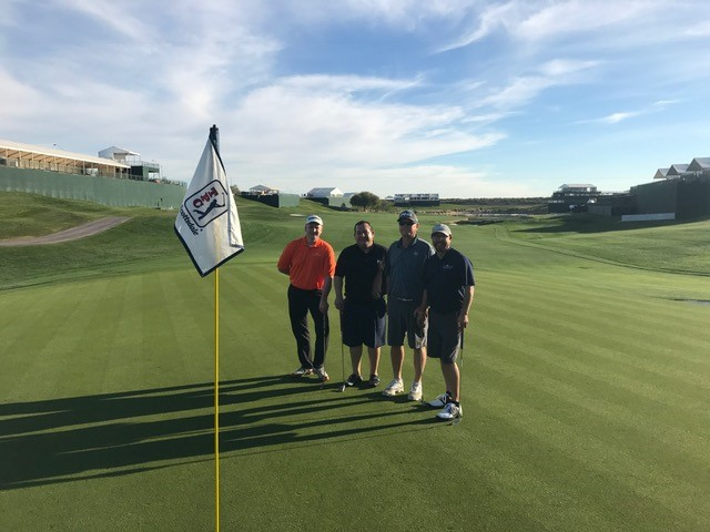 four golfers stand on the green near a hole