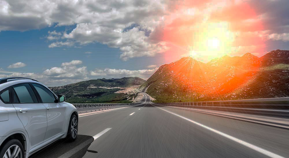 Car on the highway with a red and orange camera flare in the top right