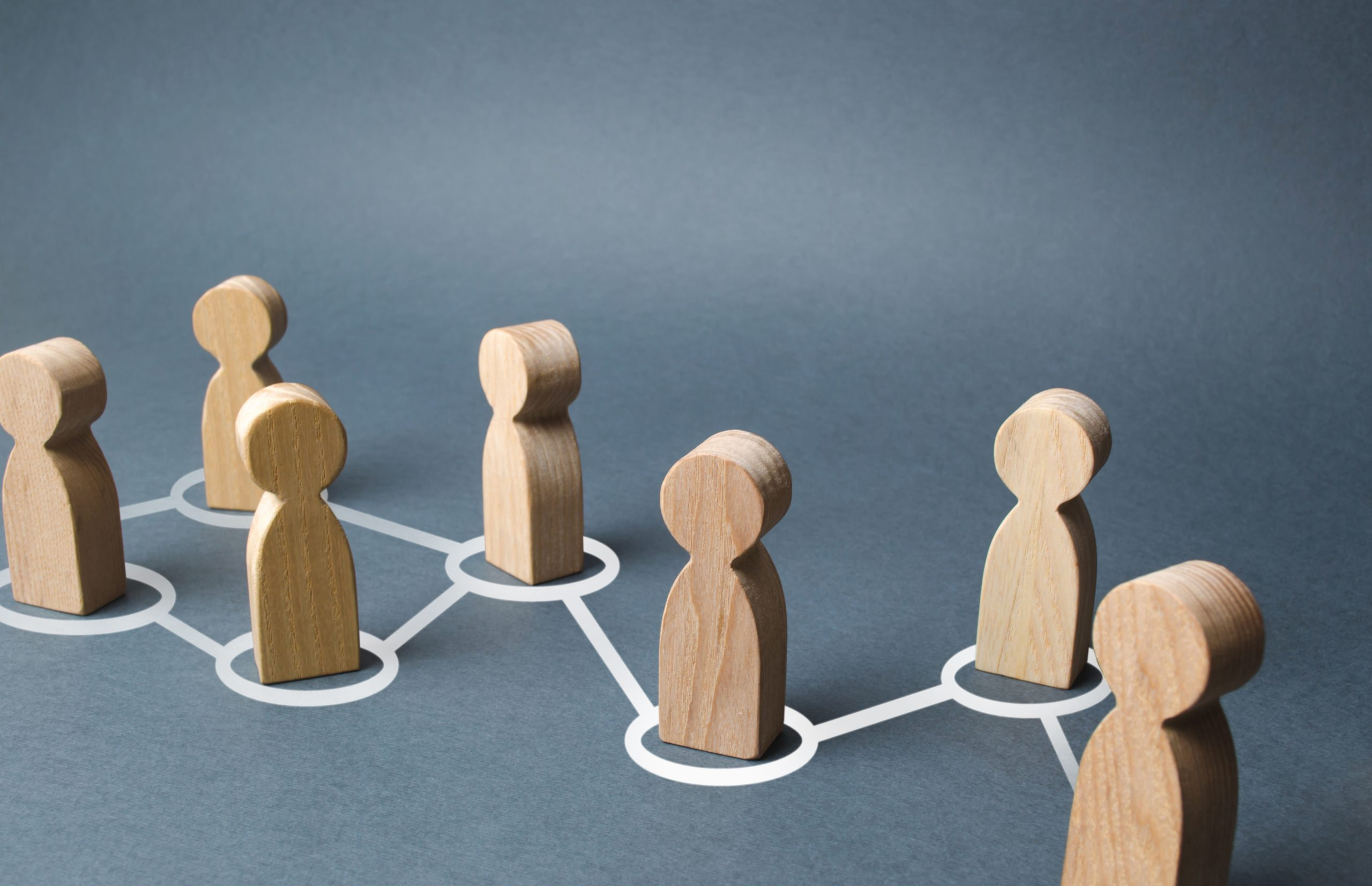 Chain of people figurines connected by white lines. Cooperation and interaction between people and employees. Dissemination of information in society, rumors. Communication. social contacts