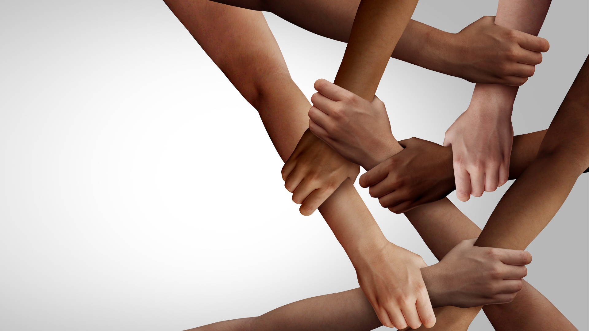 Multiple hands of different ethnicities intersecting and holding each other